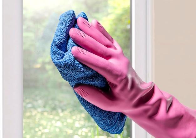 Hände in gummihandschuhen und in mikrofasertuch, die fensterglas säubern