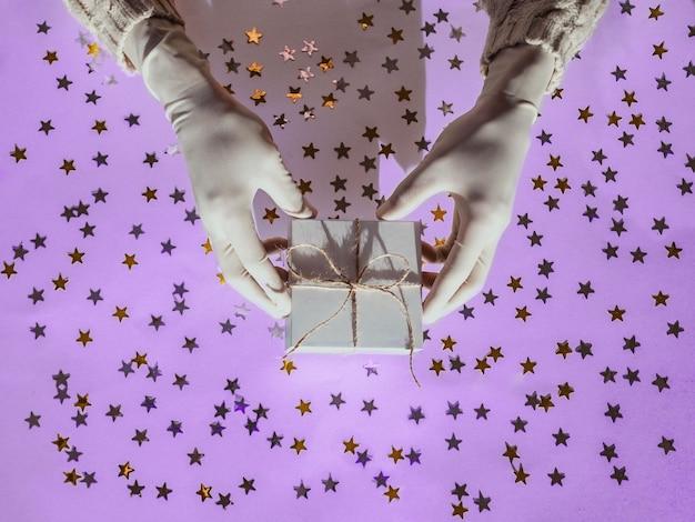 Hände in gummischutzhandschuhen halten eine weiße geschenkbox goldene und silberne konfettisterne
