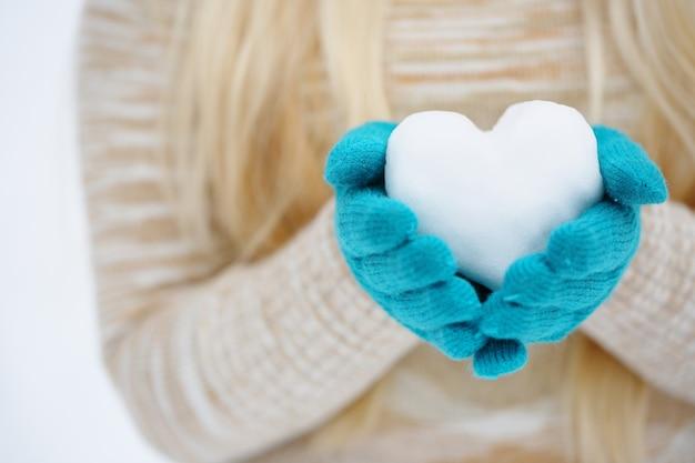 Hände in handschuhen halten das herz vom schnee fern