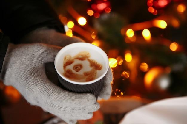 Hände in handschuhen halten eine heiße tasse kaffee kaffee für den winter