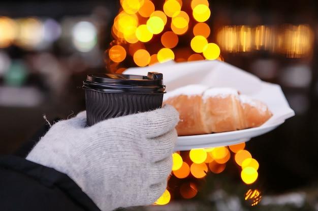 Hände in handschuhen halten eine heiße tasse kaffee und ein croissant. kaffee zum mitnehmen im winter