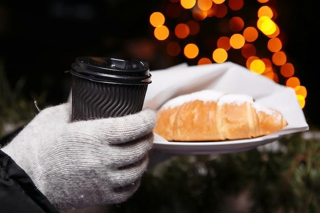 Hände in handschuhen halten eine heiße tasse kaffee und ein croissant