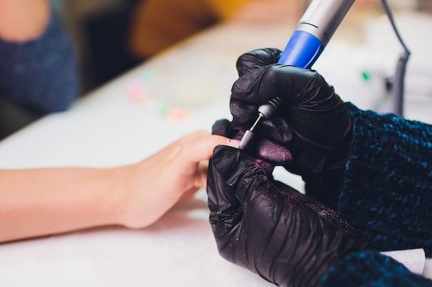 Hände in handschuhen kümmern sich um die handnägel des mannes. maniküre-schönheitssalon.