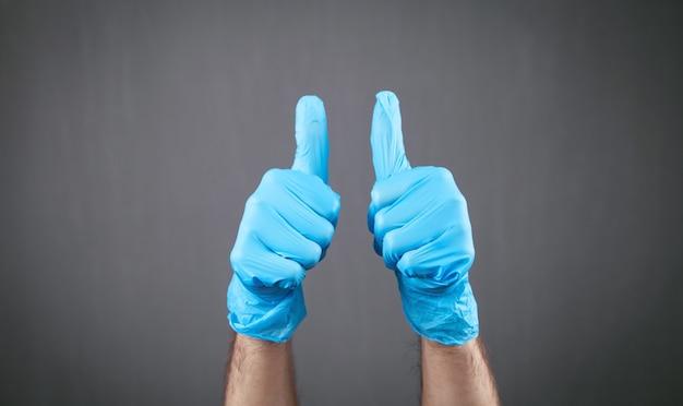 Hände in medizinischen handschuhen, die daumen nach oben machen.