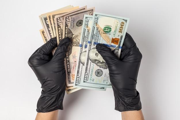 Hände in medizinischen handschuhen, die eine packung dollar halten. das konzept der infektion für geld, schmutziges geld