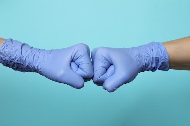 Hände in medizinischen handschuhen, die mit fauststoß auf blauem lokalisiertem hintergrund grüßen