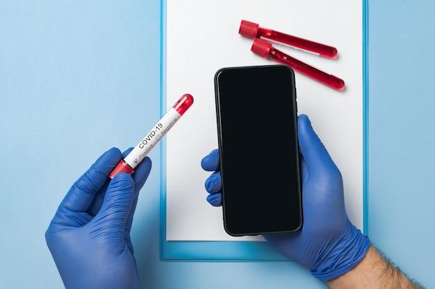 Hände in medizinischen handschuhen, die smartphone mit leerem bildschirm und reagenzglas mit blut halten. covid-19-infektionskrankheit