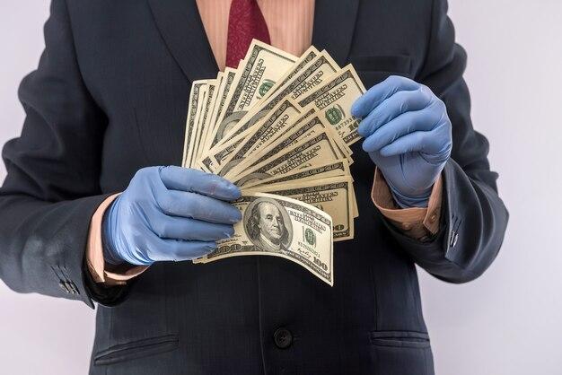 Hände in medizinischen handschuhen, die stapel-dollar für sicherheit, schmutzige geld-epidemie halten. alles für die gesundheit