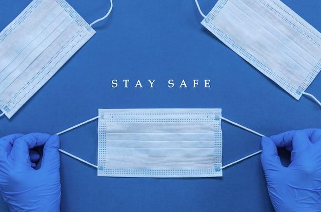 Hände in medizinischen handschuhen halten hygienemaske, chirurgische maske zum schutz vor covid-19 coronavirus und worte bleiben sie zu hause bleiben sie sicher, konzept der selbstquarantäne hintergrund