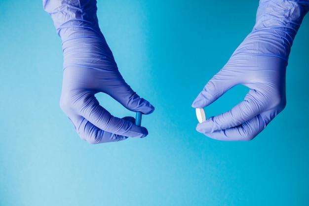 Hände in medizinischen handschuhen halten pillen