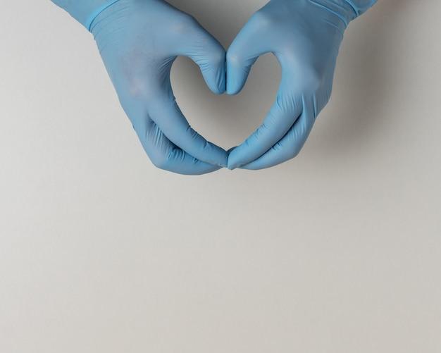 Hände in medizinischen handschuhen in form des herzens auf weiß mit kopienraum.