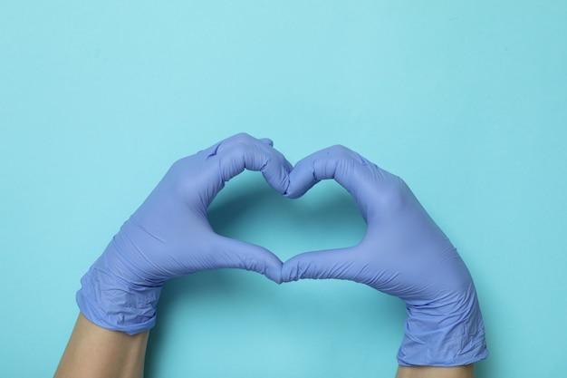 Hände in medizinischen handschuhen zeigen herz auf blauem isoliertem hintergrund
