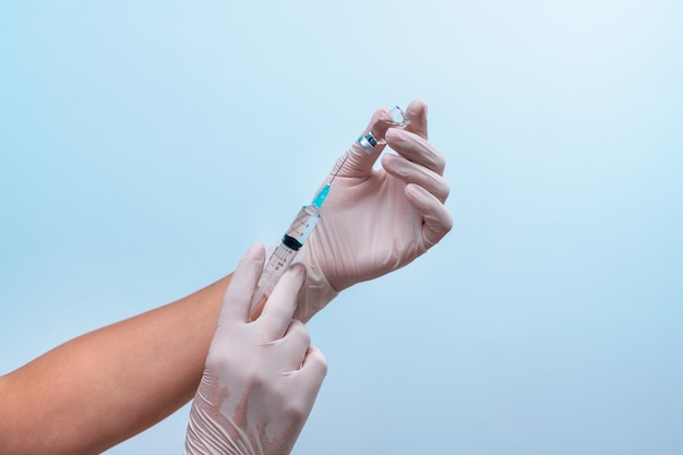 Hände in medizinischen latexhandschuhen entnehmen medizin aus einer ampulle. das konzept der pharmakologie.