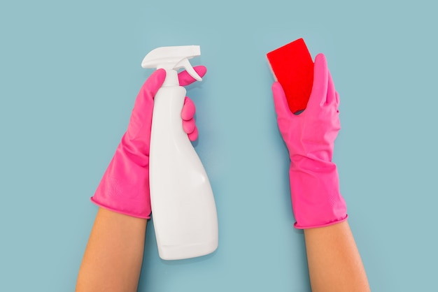 Hände in rosa handschuhen halten einen waschmittelspender und einen waschlappen. blauer hintergrund. reinigungskonzept.