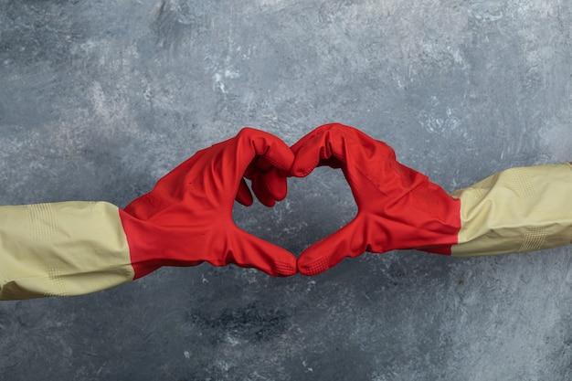 Hände in roten schutzhandschuhen geben herzzeichen.
