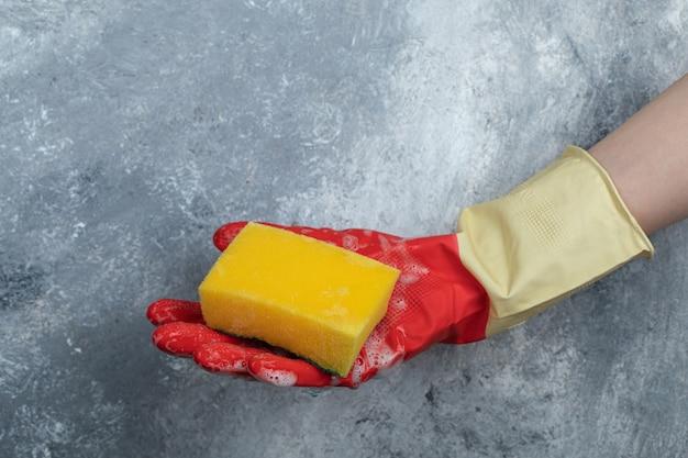 Hände in roten schutzhandschuhen halten schwamm.