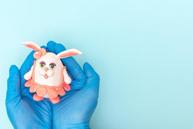 Hände in schützenden medizinischen handschuhen, die einen hausgemachten osterhasen in einem rosa rock auf einem blauen hintergrund halten