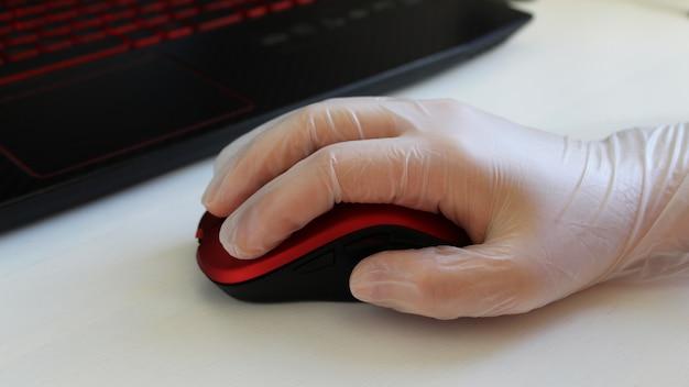 Hände in schutzhandschuhen mit einer maus