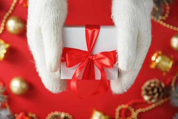 Hände in weißen strickhandschuhen, die ein geschenk auf einem roten hintergrund halten. weiße box mit rotem band. nachhaltiger urlaubslebensstil. weihnachtsdekorationen