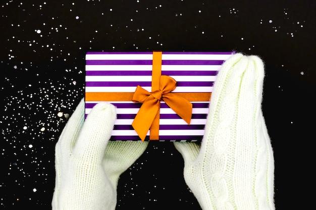 Hände in weißen winterhandschuhen, die eine gestreifte geschenkbox mit einer satinorangen schleife auf einem schwarzen schneebedeckten hintergrund halten. konzept weihnachten und neujahr.