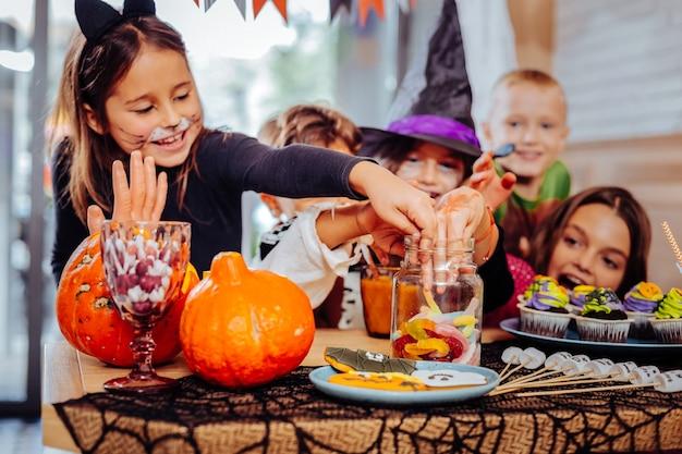 Hände ins glas. kinder, die kostüme tragen, legen ihre hände in glas mit gummiwürmern, die halloween-partys besuchen