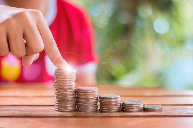 Hände junger asiatischer mädchen, die geld auf der treppe sparen lernen sie, geld zu sparen, verwenden sie das konzept des sparens