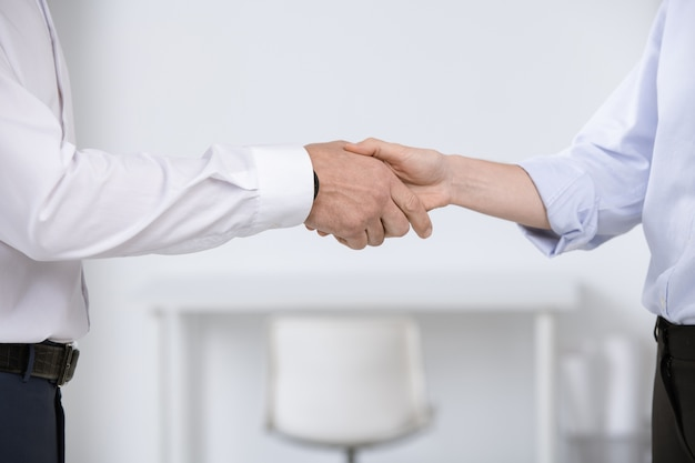 Hände junger geschäftspartner, die sich gegenseitig durch treffen oder nach verhandlung und vertragsunterzeichnung begrüßen