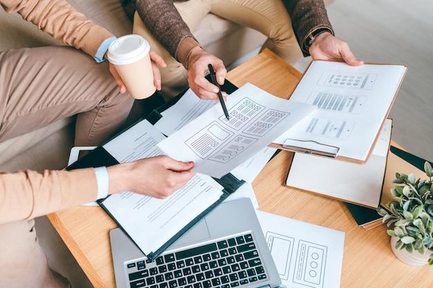 Hände junger kreativer designer oder entwickler, die am arbeitsplatz über papiere mit neuen softwarebeispielen diskutieren