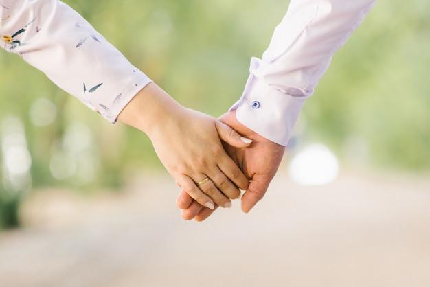 Hände kerl und mädchen, männer und frauen, braut und bräutigam, halten sich gegenseitig. romantisches paar. ehe und unterstützung