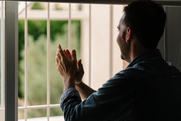 Hände klatschen im fenster für coronavirus-ärzte und gesundheitsdienste und alle, die sich der viruskrone opfern