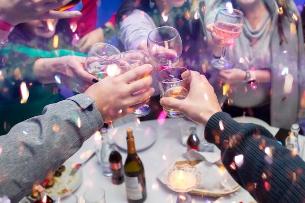 Hände klirren mit champagner und süßigkeiten. mit einer gruppe von menschen ein freudiges ereignis feiern.