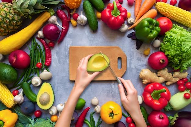 Hände kochen gesundes buntes würziges gewürztes gewürz mit frischen sommerlichen organischen antioxidansfrüchten und -gemüse für vegane oder vegetarische rezepte lokalisiert auf grauem hintergrund. gesundes lebensstilkonzept