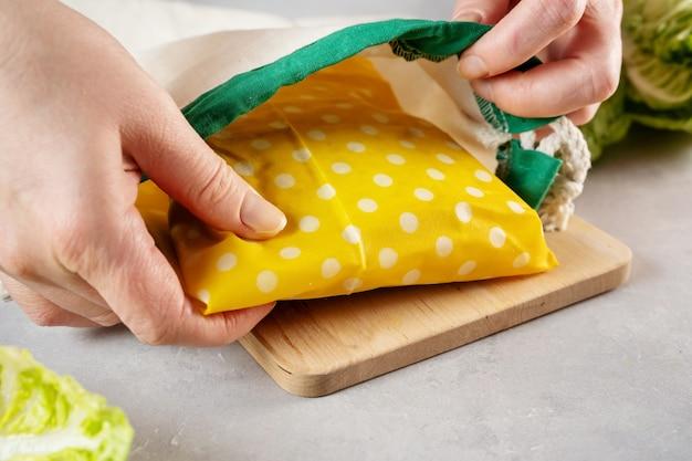 Hände legen sandwich in bienenwachs tuch gewickelt in wiederverwendbare baumwolltasche