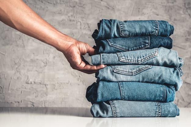 Hände, legen sie den stapel blue jeans auf grau