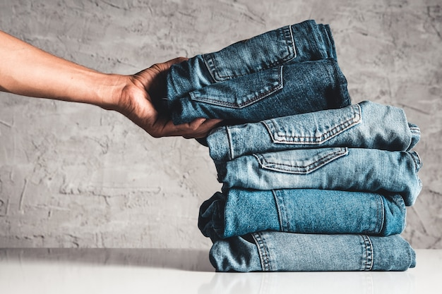 Hände, legen sie den stapel blue jeans auf grauen hintergrund.