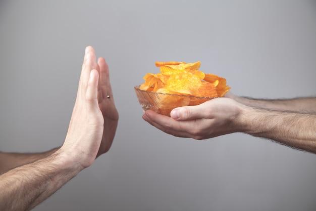 Hände lehnen leckere kartoffelchips ab.