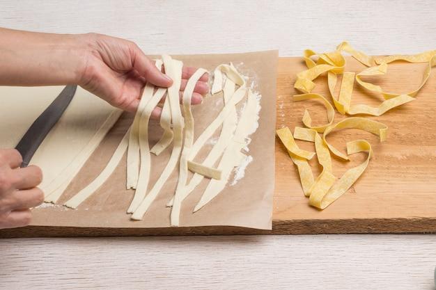 Hände machen frische pasta handgemacht. gerollter teig, in streifen geschnitten