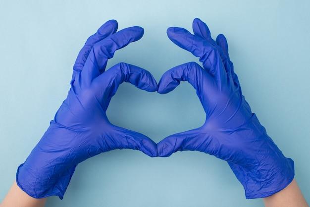 Hände machen herz und tragen blaue gummihandschuhe