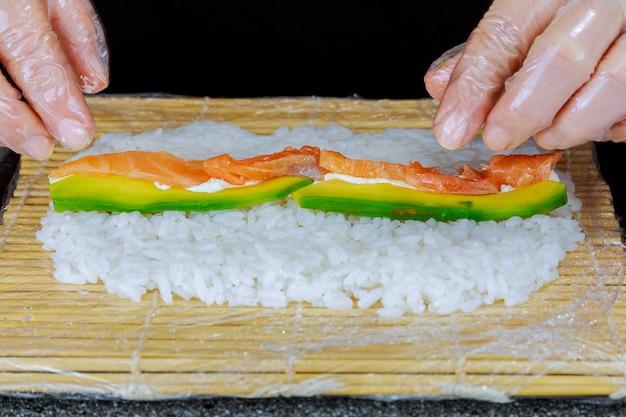 Hände machen japanische sushi-rolle mit lachs und avocado
