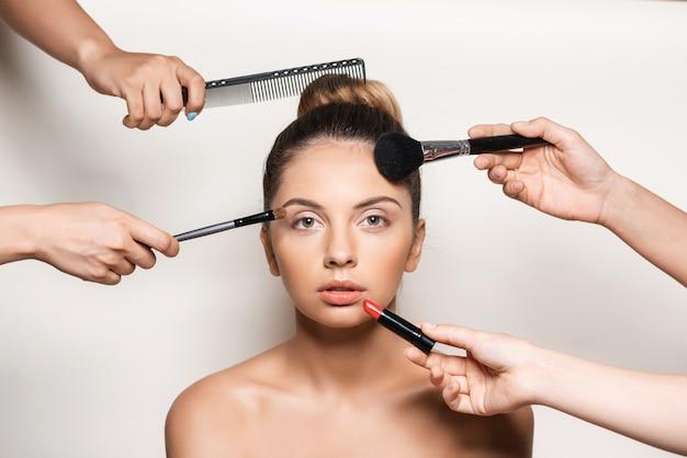 Hände machen make-up und frisur der jungen schönen frau