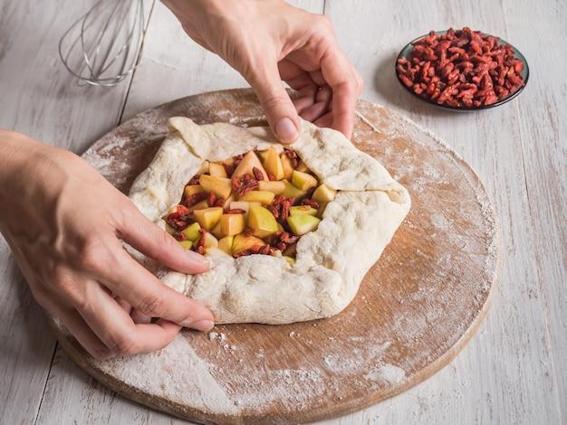 Hände machen teig apfelkuchen oder goji beere. apfelkuchen für den urlaub.