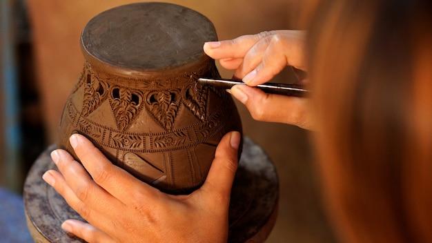 Hände machen töpfer zu einem dekorativen muster auf steingut