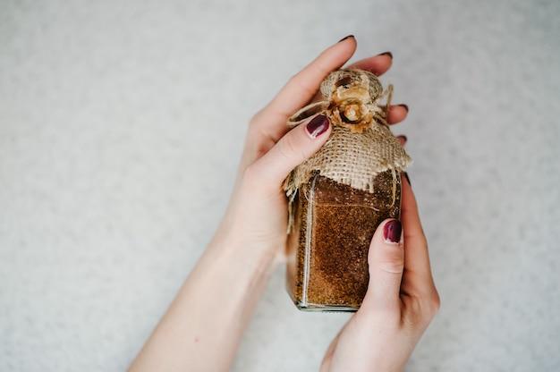 Hände mädchen, das ein kleines glas oder flaschen mit naturkosmetik hält.