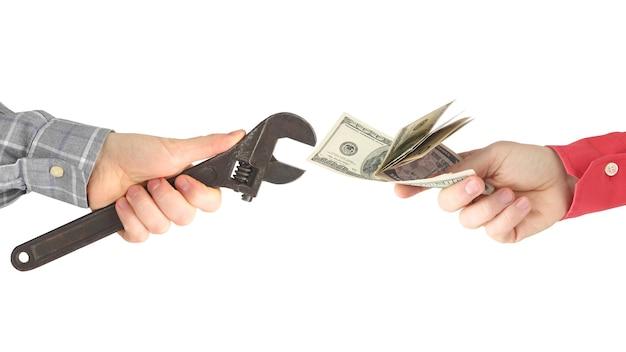 Hände mit arbeitswerkzeug und geld auf einem weißen raum. gehalt. geschäftsbeziehung.
