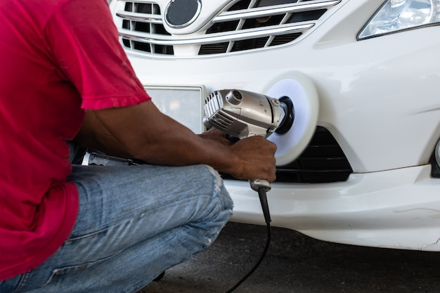 Hände mit dem augenhöhlenpolierer, der weißes auto poliert. autodetails und waschkonzept.