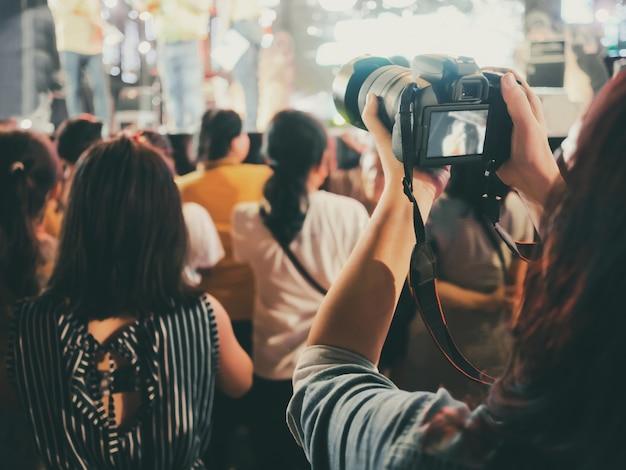 Hände mit der digitalkamera, die foto in stadium des musikkonzerts macht