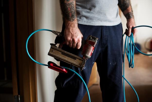 Hände mit der tätowierung, die eine ausrüstungsmaschine anhält