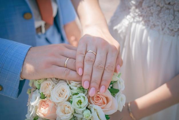 Hände mit eheringen auf hochzeitsstrauß aus rosa und weißen rosen hautnah.