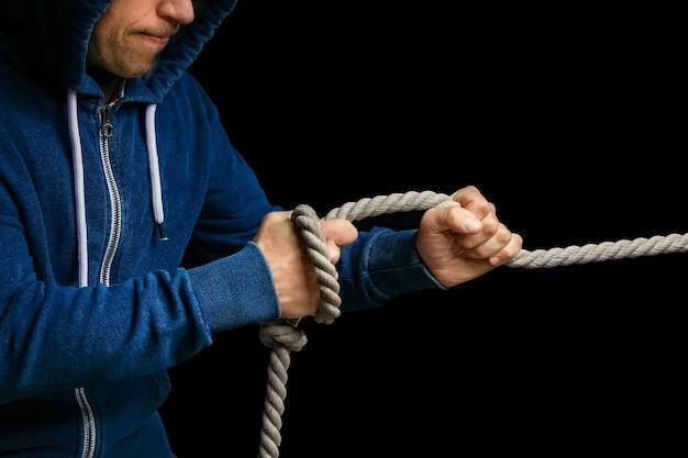 Hände mit einem seil an einer schwarzen wand. ein mann zieht ein seil wrestling. ziehen sie das geschäft auf ihre seite.