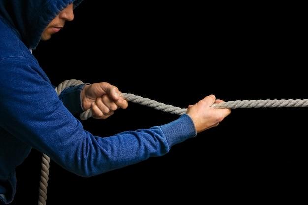 Hände mit einem seil auf einem schwarzen hintergrund. ein mann zieht ein seil wrestling. ziehen sie das geschäft auf ihre seite.